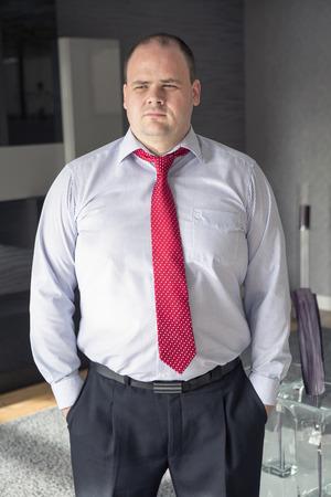 man in overhemd en stropdas staan in de woonkamer en zoekt doordachte