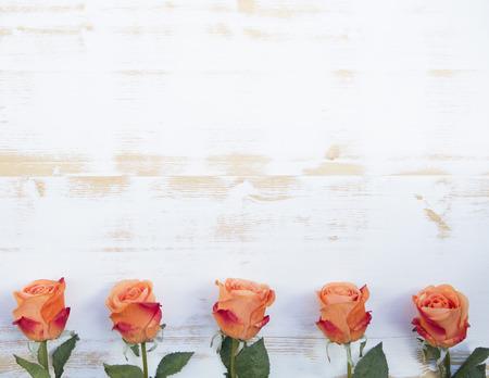 rosas naranjas: hermosas rosas naranjas se alinearon en una fila en un fondo de madera vintage Foto de archivo