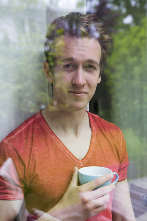 man looking out: portrait of a young blond man looking out of a window with a cup in his hands