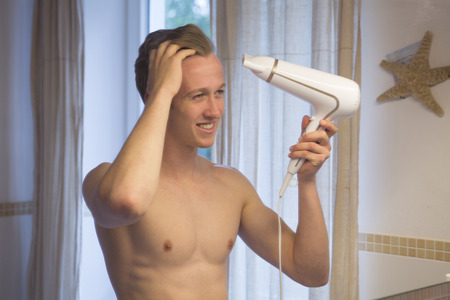 blow dry: blond shirtless man blow dry his hair in bathroom