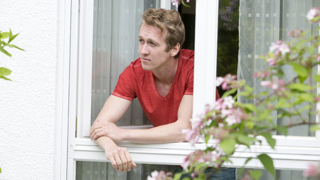 man looking out: portrait of a young blond man looking out of a window