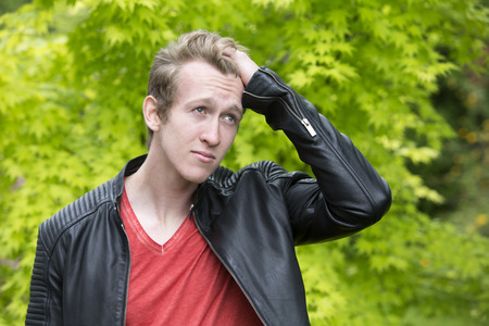 portrait of a young blond man in a black leather jacket