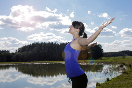 arms wide open: young woman in workout clothes standing by a lake with her arms wide open