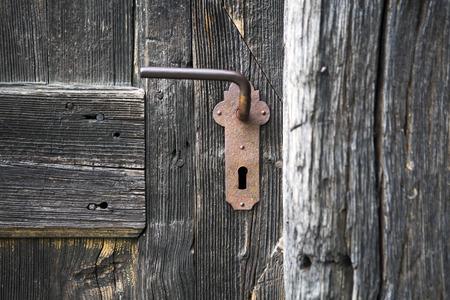 アンティークのドアのハンドルと古いの木製玄関ドア
