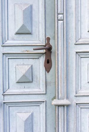 grabado antiguo: antigua puerta de entrada de madera azul con manija de la puerta antigua
