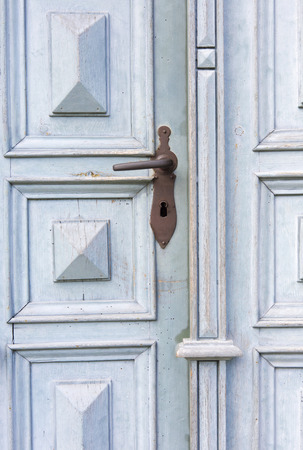 antique keyhole: old blue wooden entrance door with antique door handle