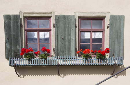 red shutters: two windows of an old house with shutters and red flowers Stock Photo