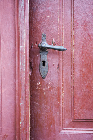 old red wooden entrance door with antique door handle