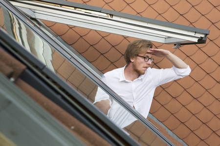 man looking out: red-haired handsome young man looking out of a rooftop window Stock Photo