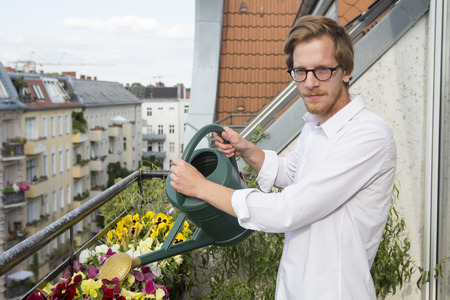 handome: red-haired handome young man watering flowers on balcony