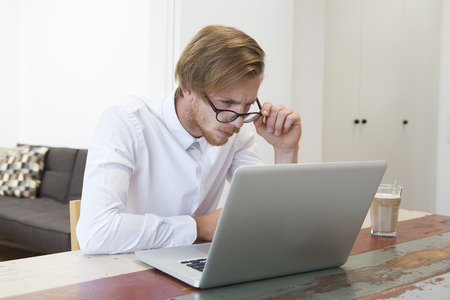 stres: red-haired young man sitting at table and looking at his laptop