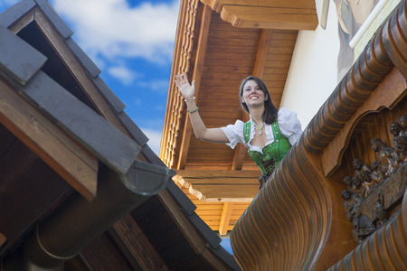 to beckon: woman in dirndl standing on balcony and beckoning to someone