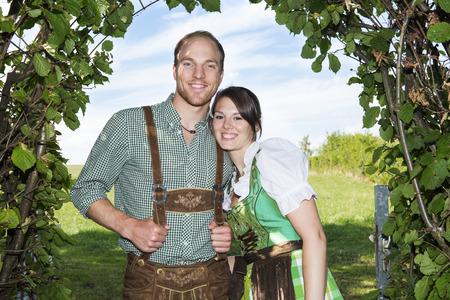 paar in traditionele Beierse kleding die zich onder een boom bevinden