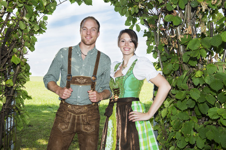 couple in traditional bavarian clothes standing underneath a tree