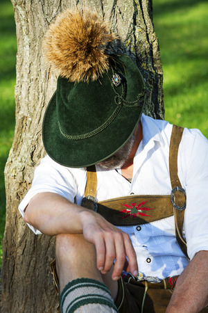 man in traditional bavarian clothes sitting by a tree and sleeps