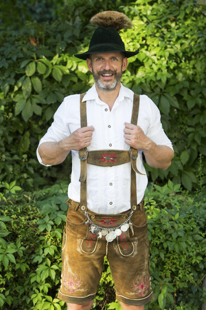 leather pants: portrait of a bavarian man with hat and leather pants