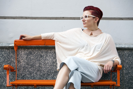 redhaired: red-haired woman sitting on a bench and relaxes Stock Photo