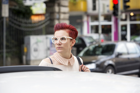 streetlife: portrait of a red-haired woman standing behind a car Stock Photo