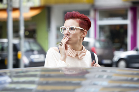 streetlife: portrait of a red-haired woman standing behind a car and smoking a cigarette
