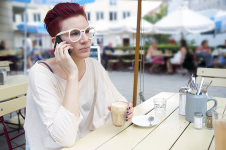 lunchbreak: red-haired woman sitting outside and talking on the phone Stock Photo