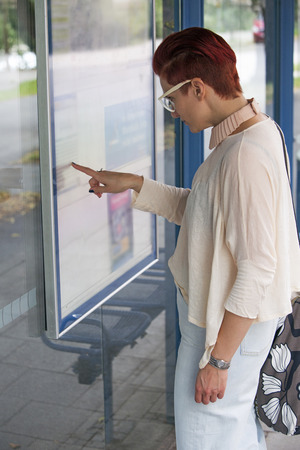 redhaired: red-haired woman at bus stop looking at timetable