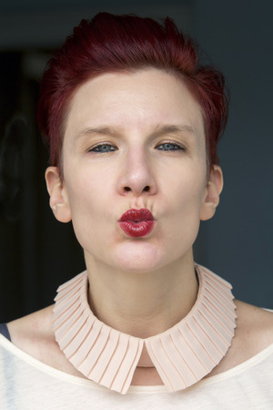 kissing lips: portrait of beautiful red-haired woman giving a kiss