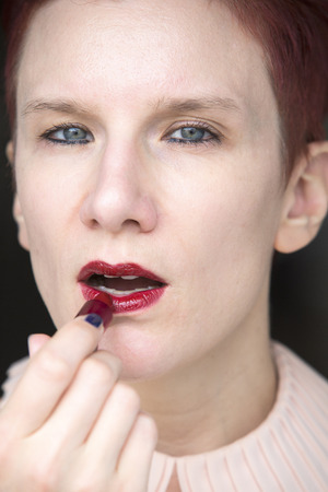 putting lipstick: portrait of redhaired woman putting red lipstick on