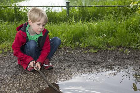 water splash: muchacho rubio joven jugando con palillo en un charco