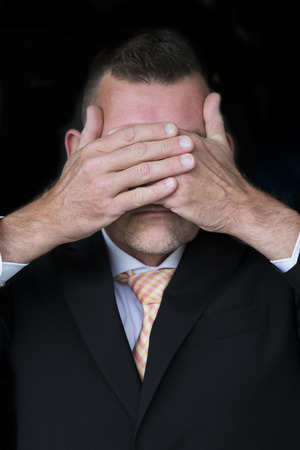 sightless: portrait of businessman with mustache covering eyes with his hands Stock Photo