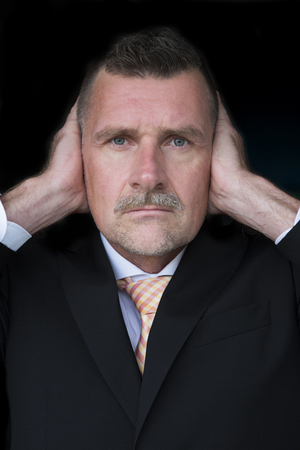 portrait of businessman with mustache covering his ears