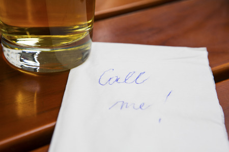 papier lettre: note on a napkin call me next to a glass of beer