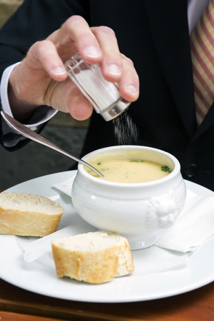 people eating restaurant: closeup of man putting salt in a bowl of cream soup