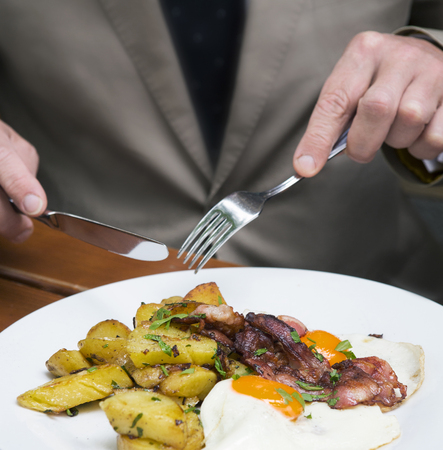 sunnyside: closeup of man in a suit eating fried eggs, potatoes and bacon