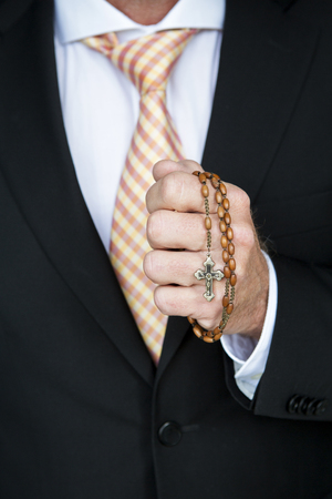 totaled: closeup of businessman holding a rosary and praying