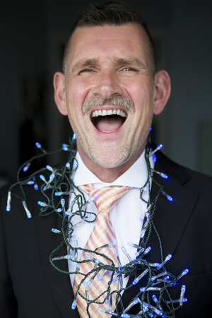 string lights: portrait of businessman with string lights and laughing