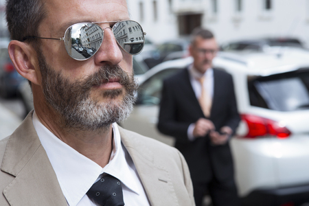 entrepeneur: closeup of man with sunglasses and businessman in the background texting with his phone