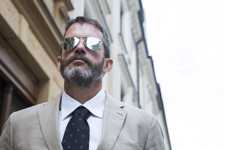 entrepeneur: portrait of businessman standing in the street wearing sunglasses