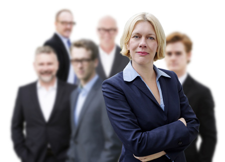 woman in suit: blond businesswoman standing in front of a group of businessmen