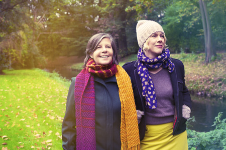 2 people: two women walking in the park in fall Stock Photo