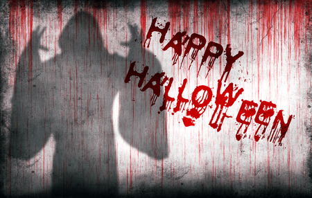 haunted: happy halloween sprayed on a bloody wall next to the shadow of a ghost Stock Photo