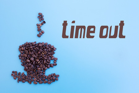 time out: Coffee beans in shape of a cup with word time out on blue background