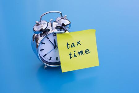 wekker op blauwe tafel met een notitie 'tax time' Stockfoto