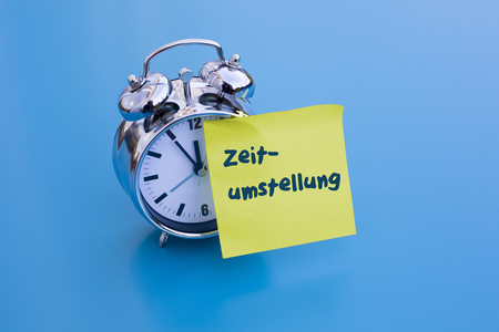 alarm clock on table with blue sticky note with German word changeover Time Change