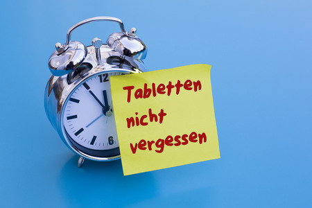 not forget: Do not forget tablets do not forget your pills alarm clock on table with blue sticky note with German Words Stock Photo