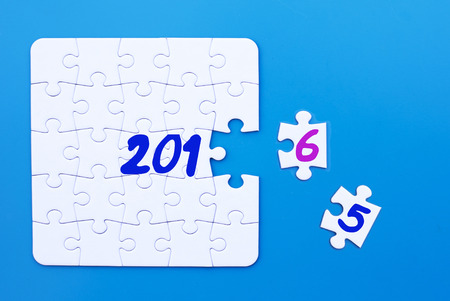 motivation icon: white puzzle on blue table with New Year 2016 Stock Photo