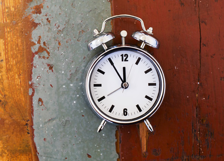 time table: alarm clock on vintage old table Stock Photo