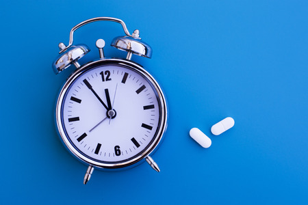 time table: alarm clock on blue table with medication
