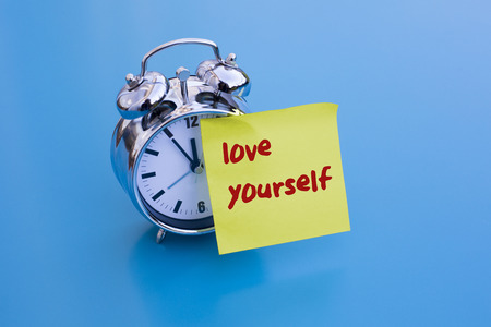 self worth: alarm clock on blue table with sticky note love yourself