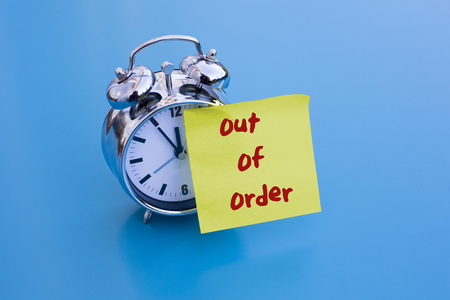 out of order: alarm clock on blue table with sticky note out of order Stock Photo