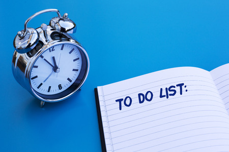 alarm clock on blue table with 'to do' list Foto de archivo